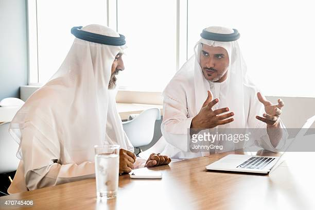 Middle Eastern Arab businessmen in traditional clothes discussing in office
