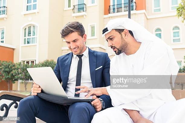 Middle Eastern Arab showing European Executive his business plan