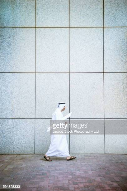 Middle Eastern architect carrying blueprints