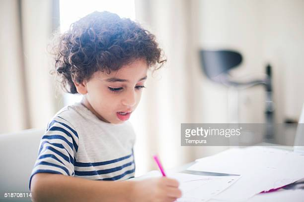 Middle eastern boy doing his homework and drawing.