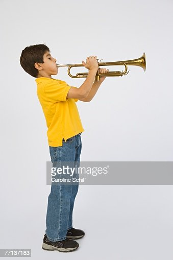Middle Eastern boy playing trumpet : Stock Photo