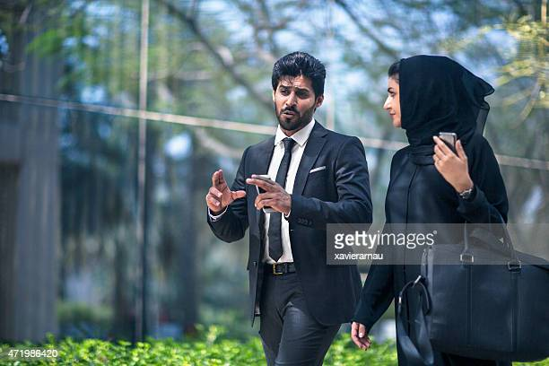 Middle Eastern business couple talking in the street