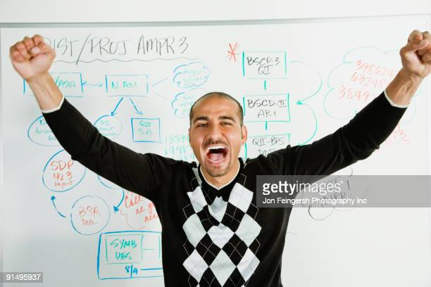 Middle Eastern businessman cheering in front of whiteboard
