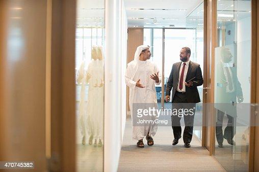 Oriente Medio hombre de negocios hablando en pasillo de trabajo de oficina