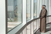 Middle eastern businessman looking out of office window