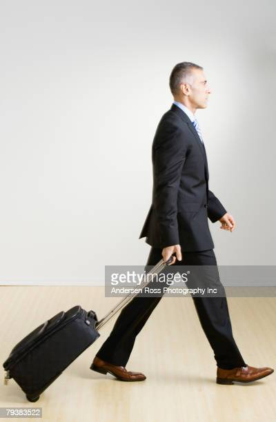 Middle Eastern businessman pulling suitcase