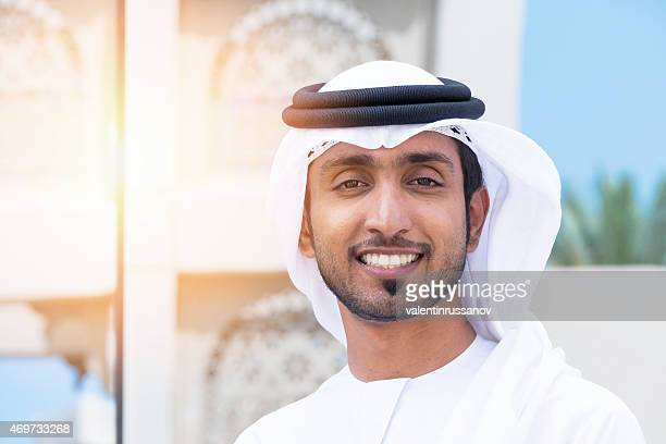 Middle Eastern businessman standing outside an office block and smile