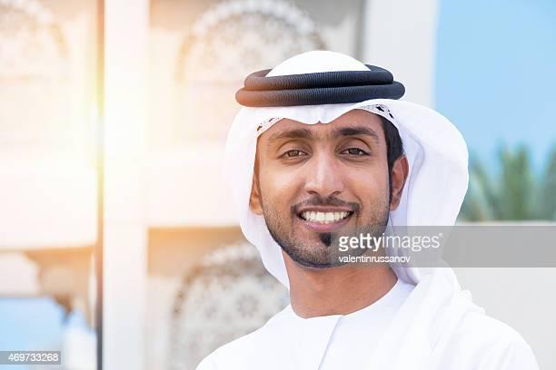 Middle Eastern hombre de negocios de pie fuera de la oficina y sonrisa bloque