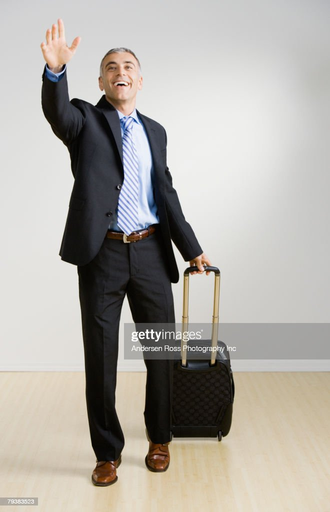 Middle Eastern businessman with suitcase waving