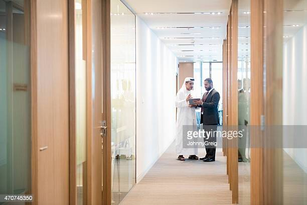 Middle Eastern businessmen discussing over tablet in office corridor