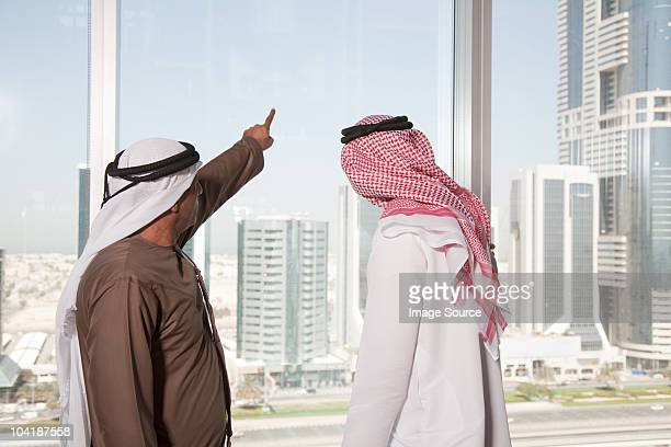 Middle eastern businessmen looking at dubai through office window