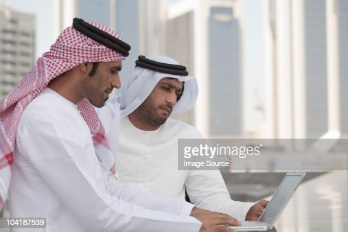 Middle eastern businessmen using laptop outdoors