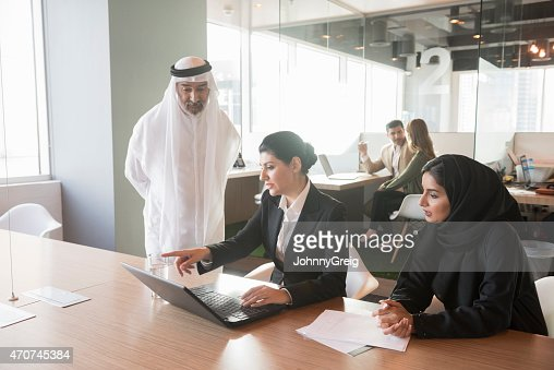 Middle Eastern businesswoman discussing over laptop with team