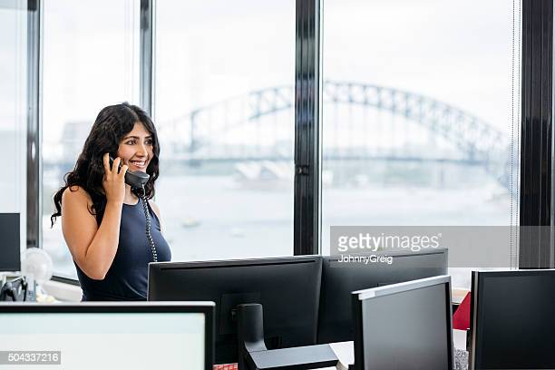 Middle Eastern businesswoman using cell phone, smiling