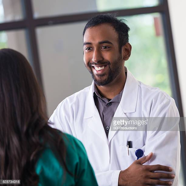 Middle Eastern doctor talking with nurse in hospital hallway