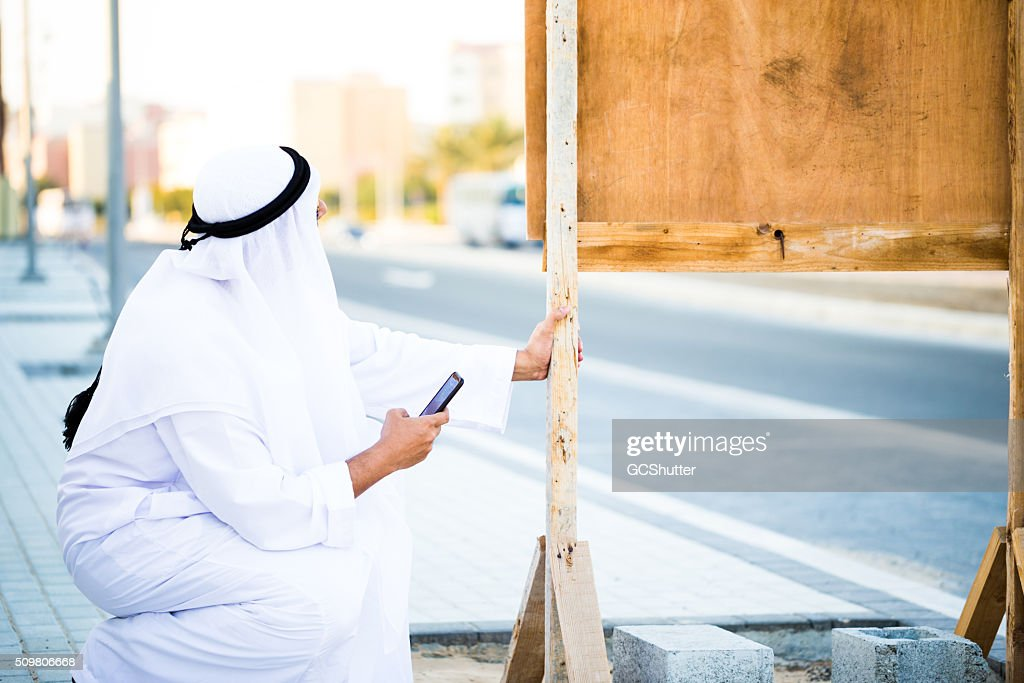 Middle Eastern Engineer Inspecting a construction notice board