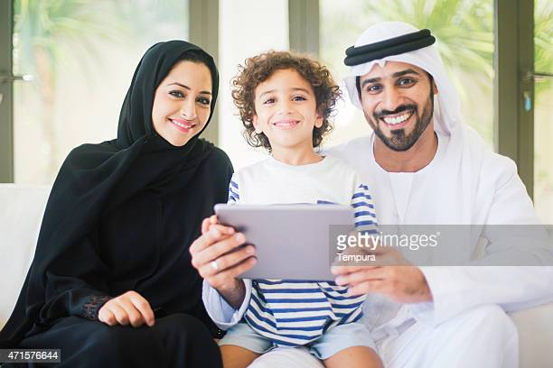 Middle eastern family posing at home with digital tablet.