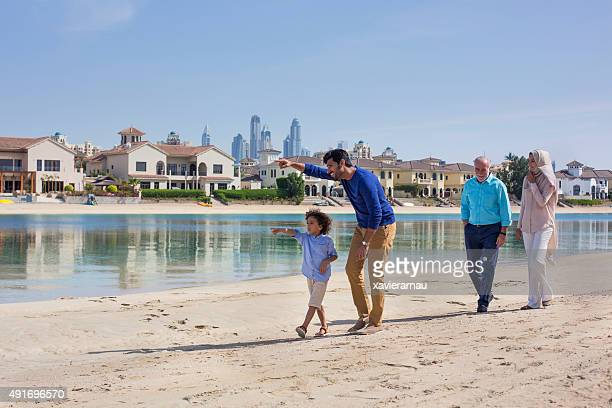 Middle eastern family walking in the beach