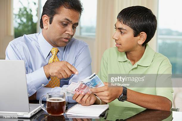 Middle Eastern father and son counting money