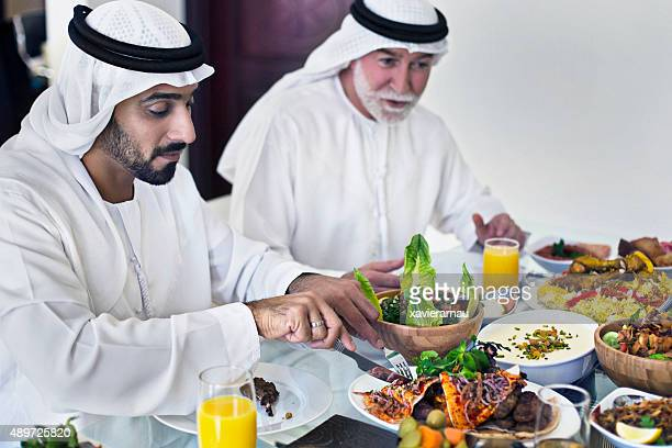 Middle Eastern father and son eating lunch