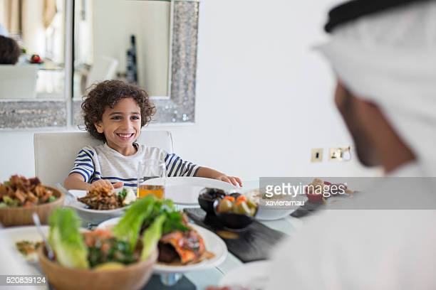 Middle Eastern father talking with his son while eating