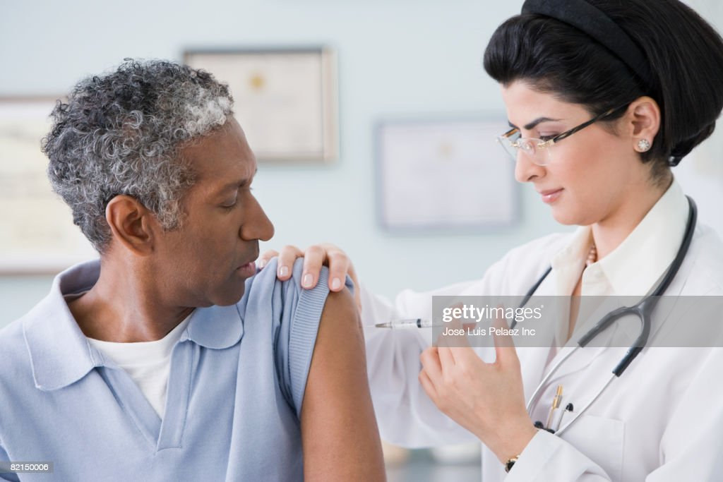 Middle Eastern female doctor giving shot to patient : Stock Photo