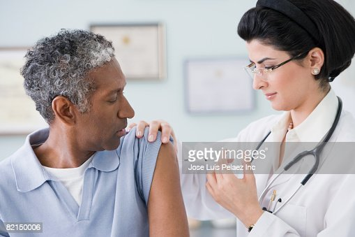 Middle Eastern female doctor giving shot to patient : ストックフォト