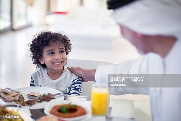 Middle Eastern grandfather talking with his grandson while eating