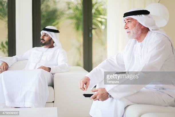 Middle eastern grandfather watching tv at home with grandson.