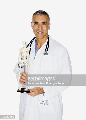 Middle Eastern male doctor holding skeleton model : Stock Photo