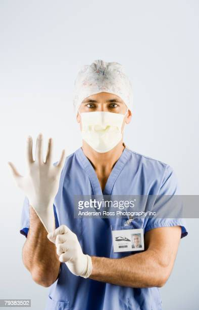 Middle Eastern male doctor putting on gloves