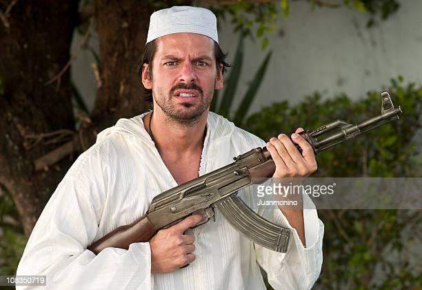 Mediorientale uomo vestito in bianco con pistola e personale