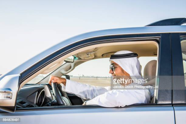 Middle Eastern man driving car