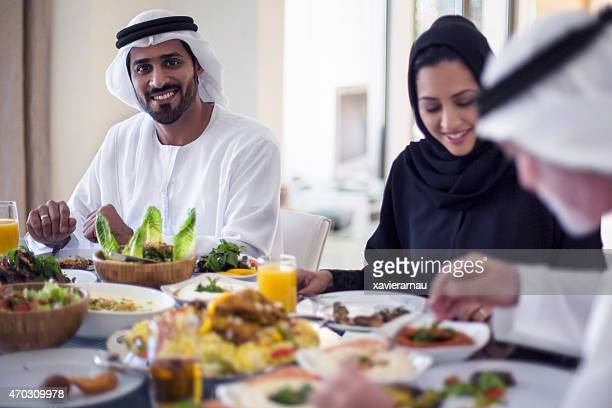 Middle Eastern man eating with family