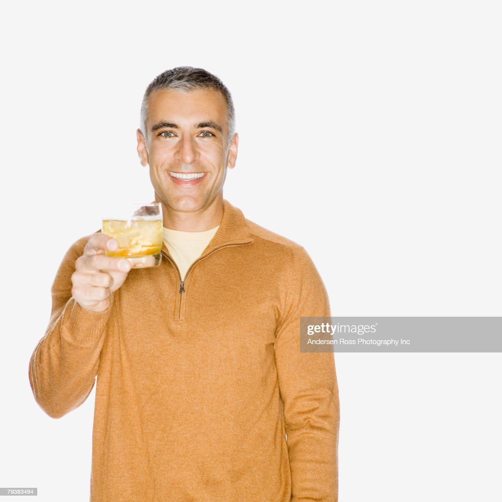 Middle Eastern man holding up drink : Stock Photo