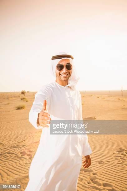 Middle Eastern man offering handshake in desert