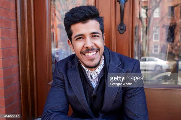 Middle Eastern man smiling on front stoop
