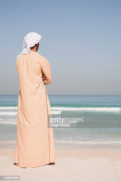Middle Eastern man standing on the beach