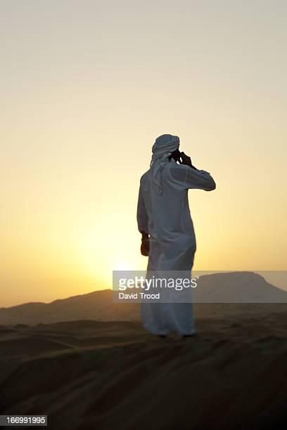 Middle Eastern man talking on in Desert near Dubai
