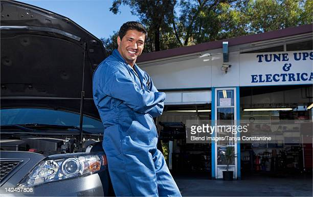 Middle Eastern mechanic leaning on car