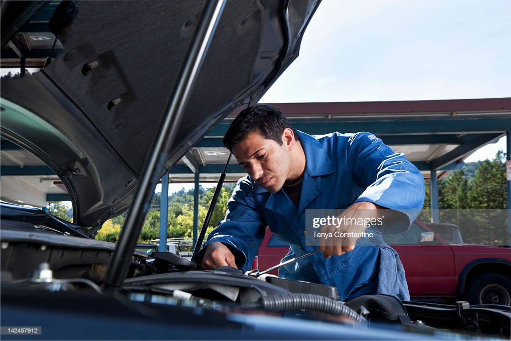 Middle Eastern mechanic working on car engine