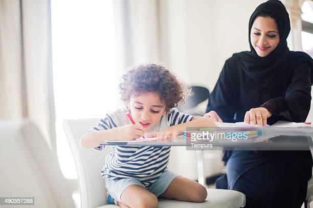 Middle eastern Mutter hilft ihr Kind bei den Hausaufgaben.