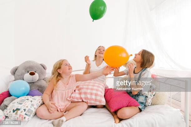 Middle Eastern sisters sitting on bed playing with balloons