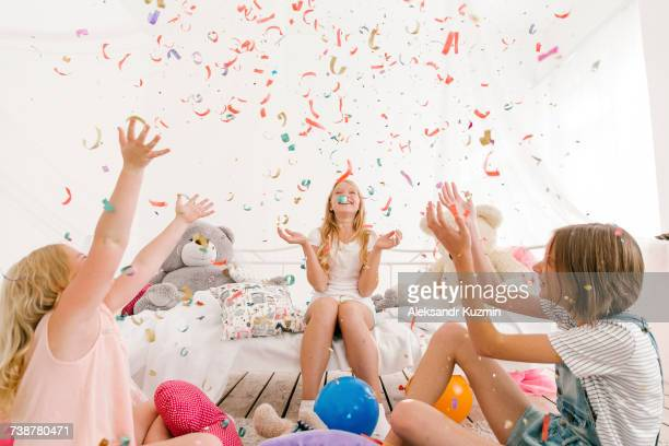 Middle Eastern sisters throwing confetti in bedroom