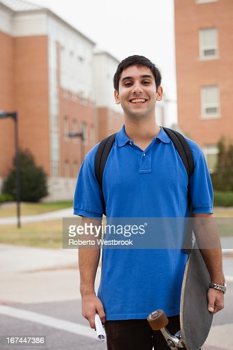 Middle Eastern student carrying skateboard : Stock Photo