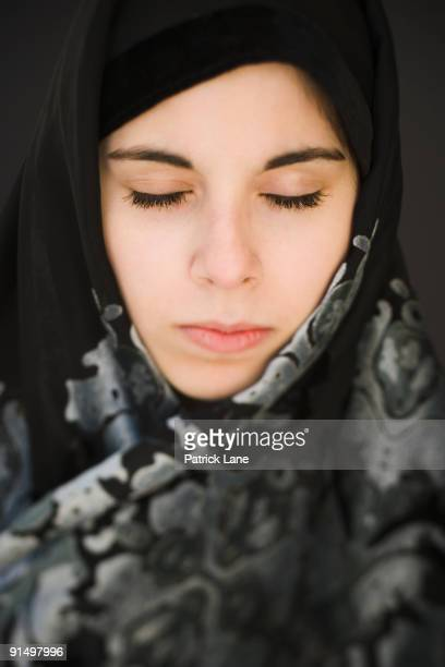 Middle Eastern teenager in headscarf with eyes closed