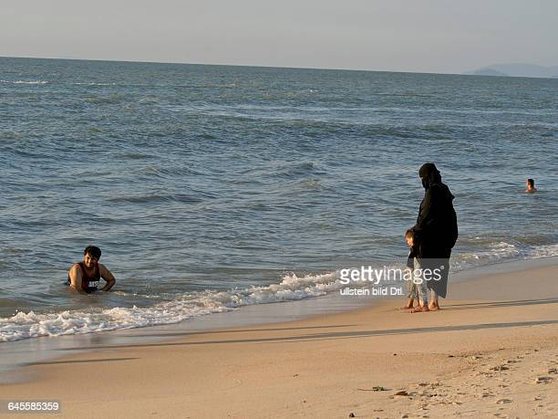 Middle Eastern tourists at Feringhi beach in Penang Malaysia with woman in full hijab burqa