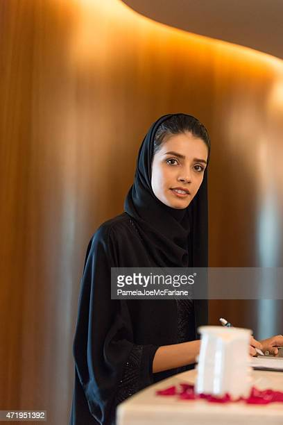 Middle Eastern Woman Checking In at Luxury Spa Reception