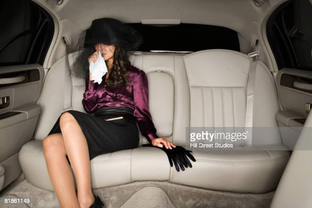 Middle Eastern woman crying in limousine