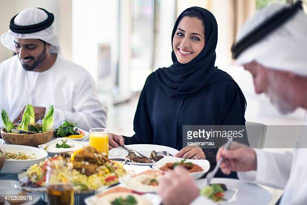 Middle Eastern woman eating with family